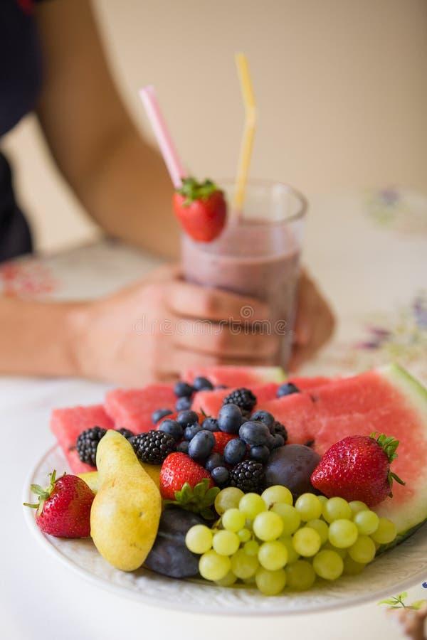 Ciérrese para arriba de la fruta orgánica del verano delicioso en la placa con una mujer en fondo Mujer que sostiene un smoothie  fotografía de archivo