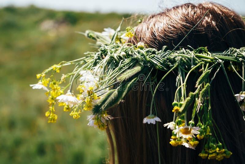 Ciérrese para arriba de la guirnalda hecha de flores salvajes, mujer joven del pelo con las flores en su pelo foto de archivo libre de regalías