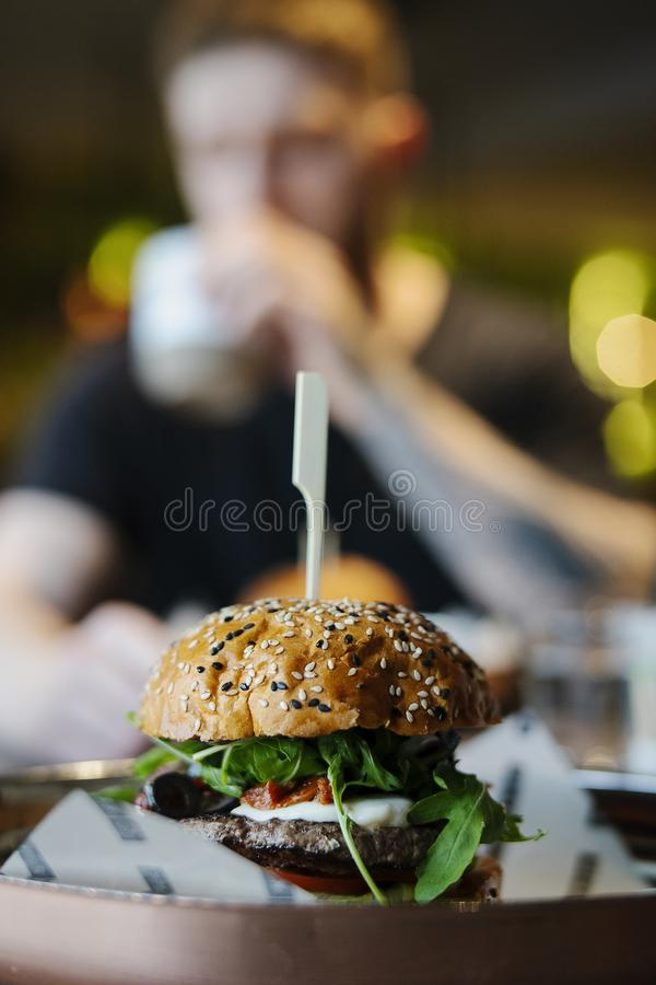 Ciérrese para arriba de la hamburguesa sabrosa grande fresca con el hombre en fondo en café imagenes de archivo