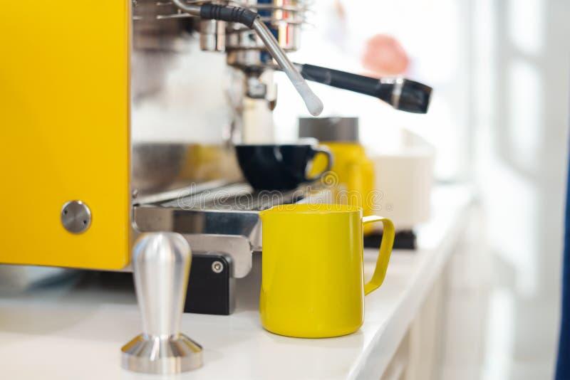 Ciérrese para arriba de la máquina moderna del café y del pincher amarillo en contador de la barra imagen de archivo