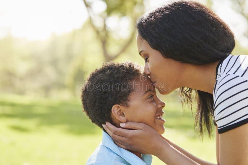 Ciérrese para arriba de la madre que besa al hijo en parque fotografía de archivo libre de regalías