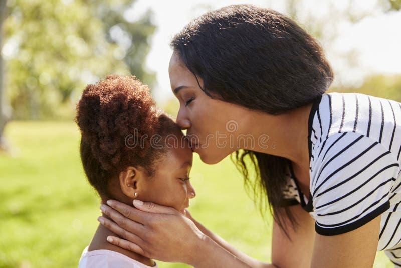 Ciérrese para arriba de la madre que besa a la hija en parque fotografía de archivo