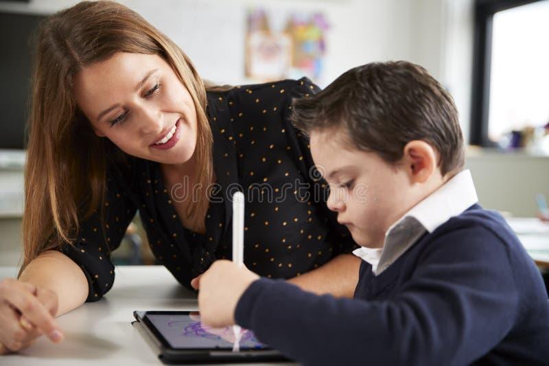 Ciérrese para arriba de la maestra joven que se sienta en el escritorio con un colegial de Síndrome de Down que usa una tableta e imagen de archivo libre de regalías