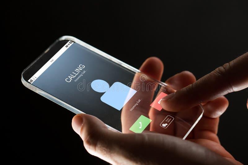 Ciérrese para arriba de la mano con llamada entrante en smartphone fotos de archivo libres de regalías