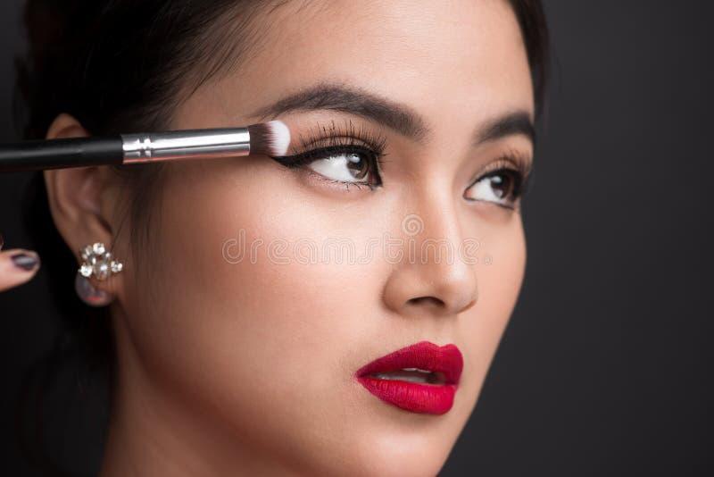 Ciérrese para arriba de la mano de la mujer asiática que aplica el sombreador de ojos en ojo femenino foto de archivo libre de regalías