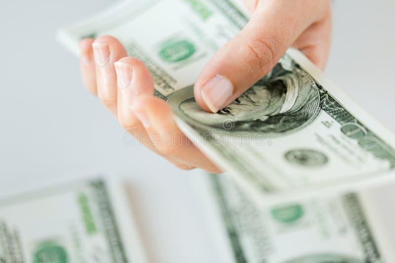 Ciérrese para arriba de la mano de la mujer que dólar cuenta dinero fotografía de archivo libre de regalías