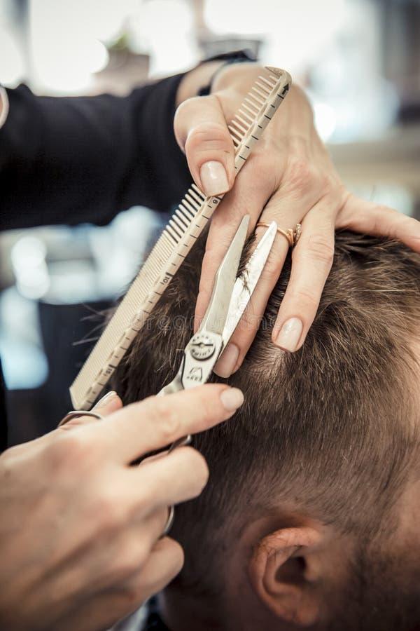 Ciérrese para arriba de la mano del cosmetólogo que da un corte de pelo al cliente masculino en la sala imagen de archivo libre de regalías