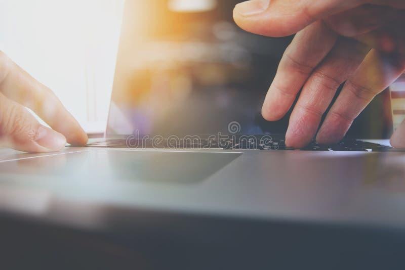 Ciérrese para arriba de la mano del diseñador que trabaja con el ordenador portátil en de madera imagenes de archivo