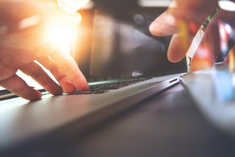Ciérrese para arriba de la mano del diseñador que trabaja con el ordenador portátil en de madera foto de archivo libre de regalías