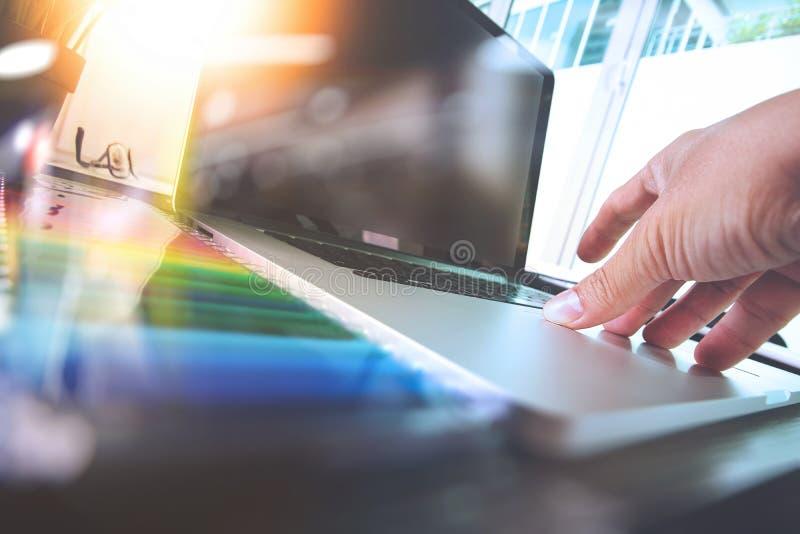 Ciérrese para arriba de la mano del diseñador que trabaja con el ordenador portátil en de madera fotos de archivo libres de regalías