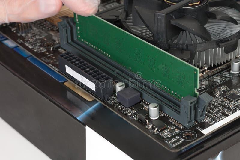 Ciérrese para arriba de la mano del hombre con el guante que instala el modul de la memoria del Ram DDR4 imágenes de archivo libres de regalías