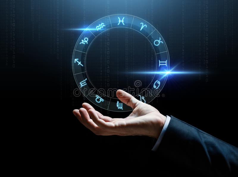 Ciérrese para arriba de la mano del hombre de negocios con las muestras del zodiaco foto de archivo