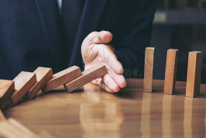 Ciérrese para arriba de la mano del hombre de negocios que para los dominós de madera descendentes ef imágenes de archivo libres de regalías