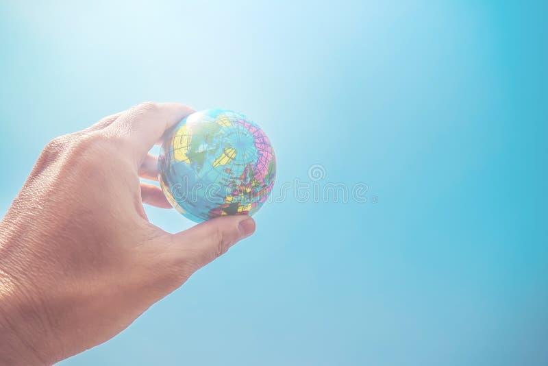 Ciérrese para arriba de la mano del hombre de negocios que muestra un pequeño globo modelo y un cielo azul imagen de archivo libre de regalías