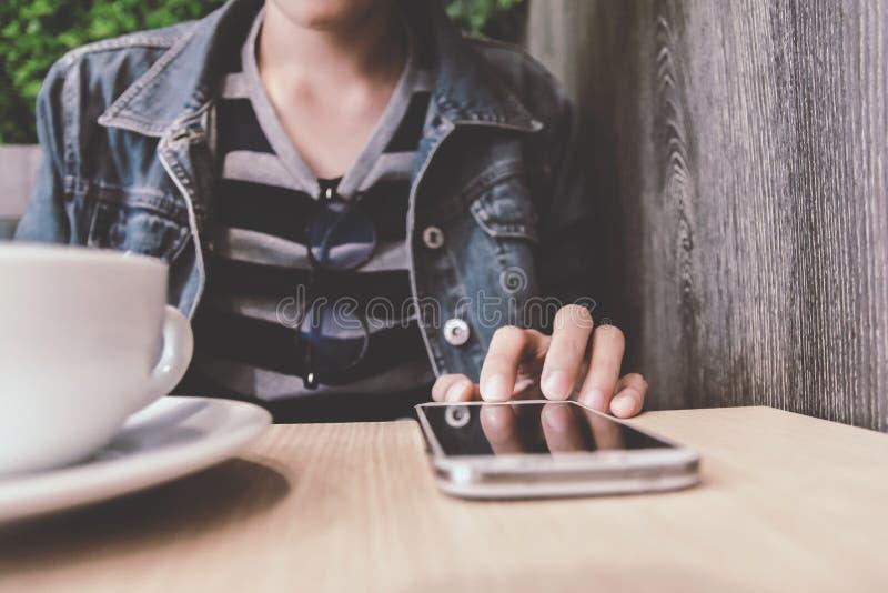 Ciérrese para arriba de la mano del hombre que celebra el tacto del teléfono móvil con el espacio en blanco de la copia para su m foto de archivo