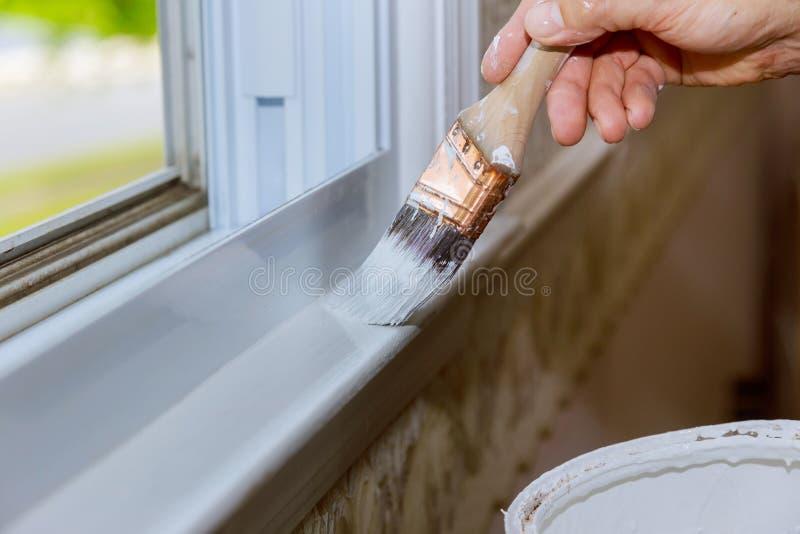 Ciérrese para arriba de la mano del hombre que pinta cuidadosamente el borde de una ventana de la casa imagen de archivo libre de regalías