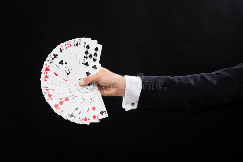 Ciérrese para arriba de la mano del mago que sostiene naipes imágenes de archivo libres de regalías