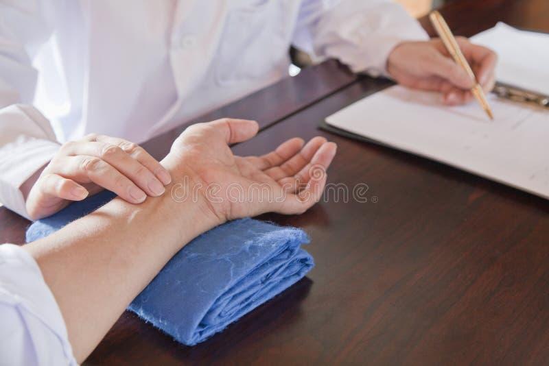 Ciérrese para arriba de la mano del paciente mientras que el doctor Takes Pulse fotos de archivo libres de regalías