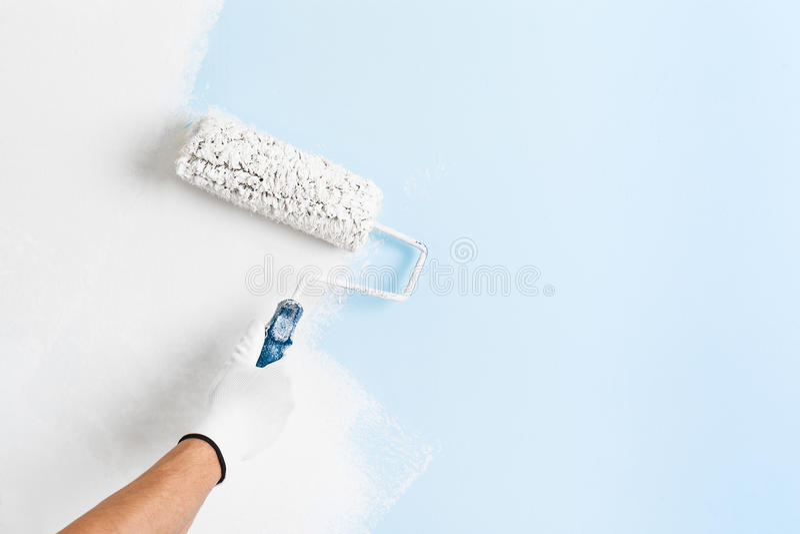 Ciérrese para arriba de la mano del pintor que pinta una pared foto de archivo