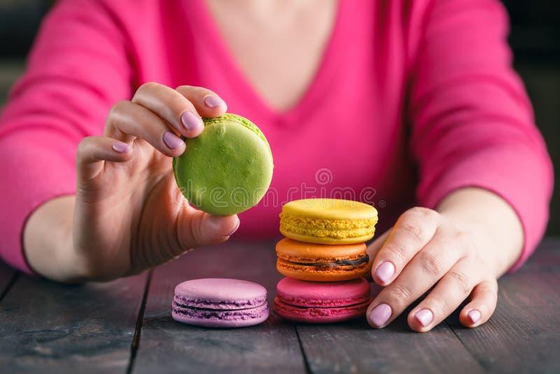 Ciérrese para arriba de la mano femenina de los pasteles que cocina los macarrones deliciosos fotos de archivo libres de regalías