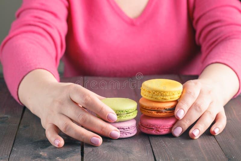 Ciérrese para arriba de la mano femenina de los pasteles que cocina los macarrones deliciosos imagenes de archivo