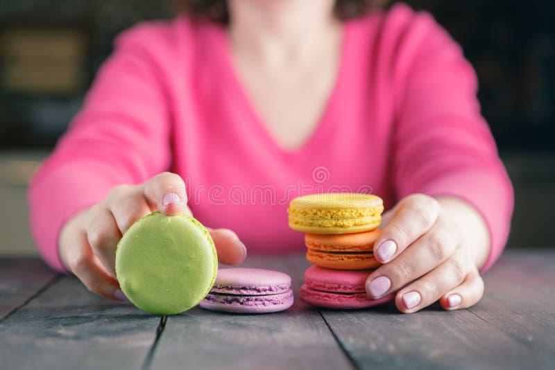 Ciérrese para arriba de la mano femenina de los pasteles que cocina los macarrones deliciosos fotografía de archivo libre de regalías