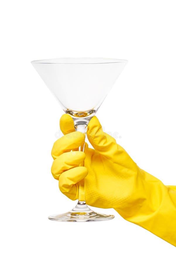 Ciérrese para arriba de la mano femenina en el guante de goma protector amarillo que sostiene martini transparente limpio de cris fotografía de archivo
