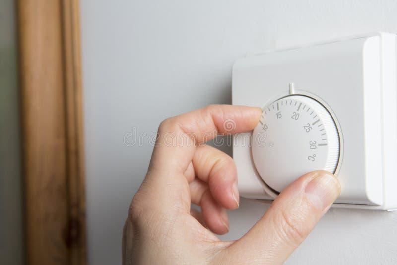 Ciérrese para arriba de la mano femenina en el termóstato de la calefacción central fotografía de archivo
