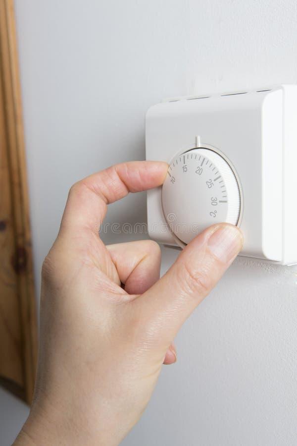 Ciérrese para arriba de la mano femenina en el termóstato de la calefacción central fotos de archivo libres de regalías