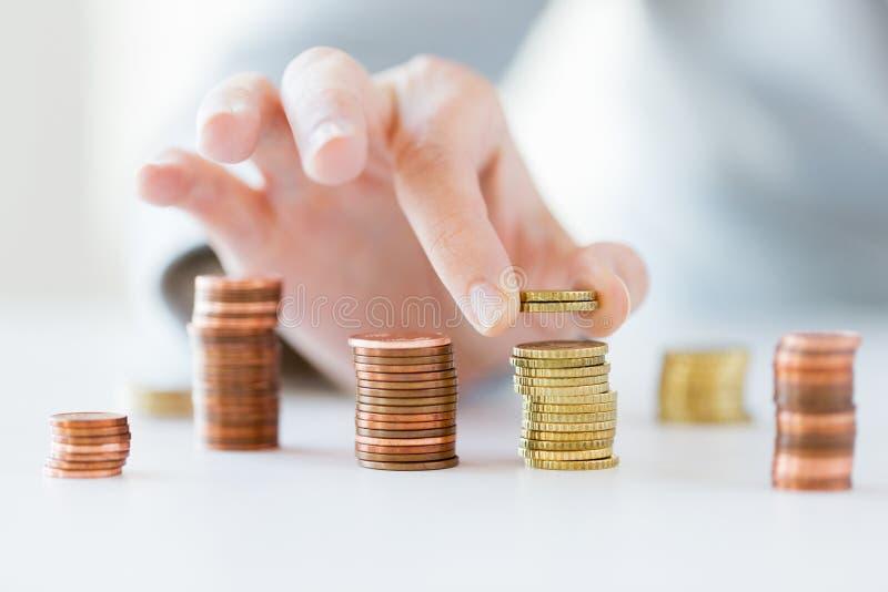 Ciérrese para arriba de la mano femenina que pone monedas en columnas imagen de archivo