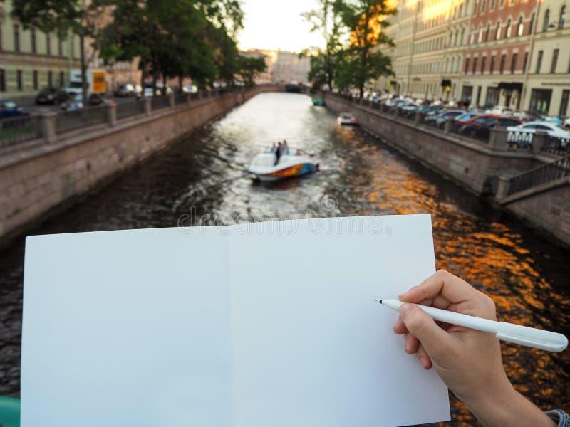 Ciérrese para arriba de la mano femenina que sostiene una pluma y abrió las páginas del sketchbook fotografía de archivo libre de regalías