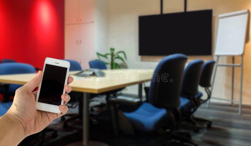 Ciérrese para arriba de la mano masculina que da el teléfono móvil elegante con la pantalla en blanco con el fondo de lujo de la  fotos de archivo libres de regalías