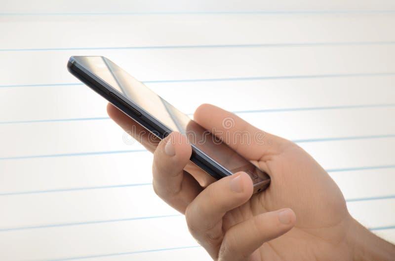 Ciérrese para arriba de la mano masculina que sostiene un teléfono elegante fotos de archivo