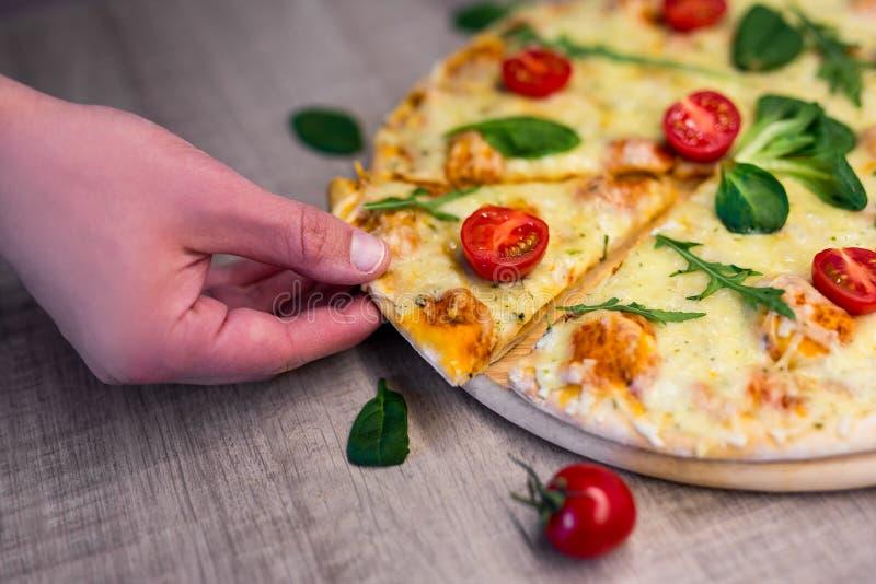 Ciérrese para arriba de la mano masculina que toma la rebanada de pizza sabrosa con los tomates y las hierbas sobre la tabla de m imagenes de archivo