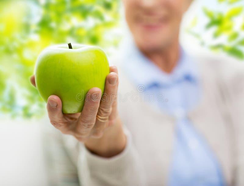 Ciérrese para arriba de la mano mayor de la mujer que sostiene la manzana verde fotos de archivo