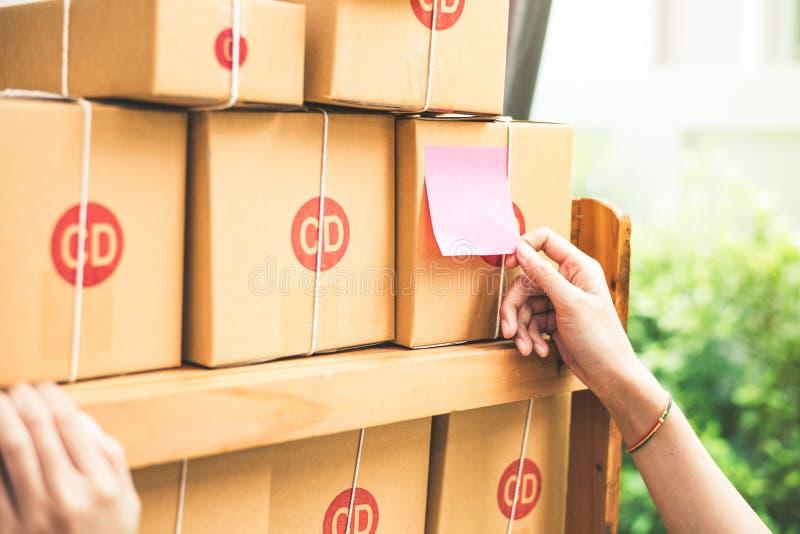 Ciérrese para arriba de la mano de la mujer al pegar el papel de la nota a los posts o al parce imagen de archivo libre de regalías
