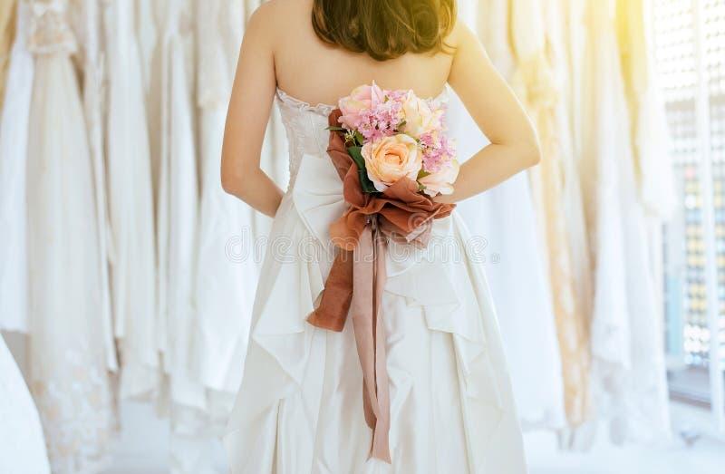 Ciérrese para arriba de la mano de la mujer de la novia que sostiene un behide del ramo su parte posterior para el momento que se imagen de archivo libre de regalías