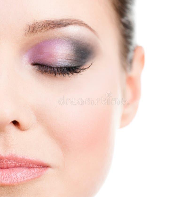 Ciérrese para arriba de la media cara de la mujer con el ojo cerrado imagen de archivo