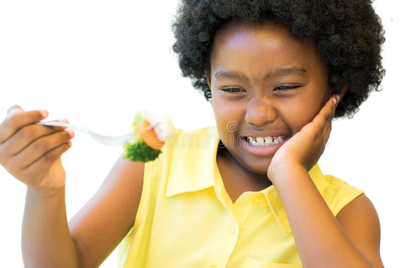 Ciérrese para arriba de la muchacha africana que rechaza verduras imagen de archivo libre de regalías