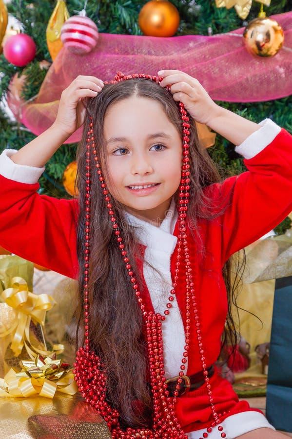 Ciérrese para arriba de la muchacha feliz que lleva un vestido rojo y que sostiene una decoración de la Navidad en sus manos sobr foto de archivo libre de regalías