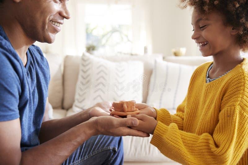 Ciérrese para arriba de la muchacha pre-adolescente que presenta un regalo hecho a mano a su padre, vista lateral fotografía de archivo libre de regalías