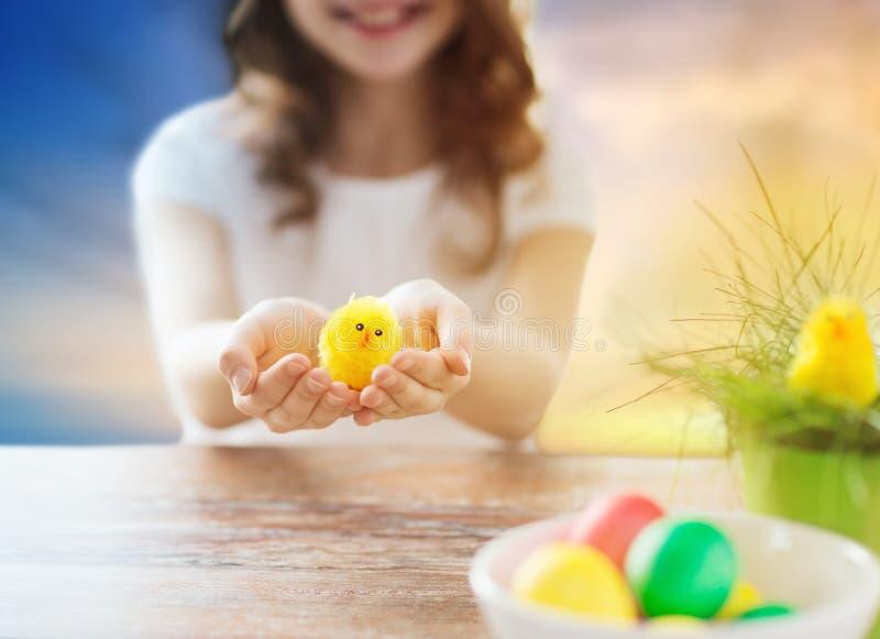 Ciérrese para arriba de la muchacha que sostiene el pollo del juguete de pascua imagenes de archivo