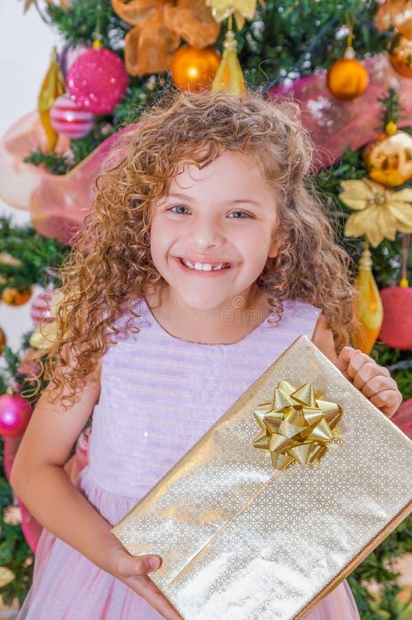 Ciérrese para arriba de la muchacha rizada sonriente que lleva un vestido rosado y que sostiene un regalo enorme en sus manos, co foto de archivo libre de regalías