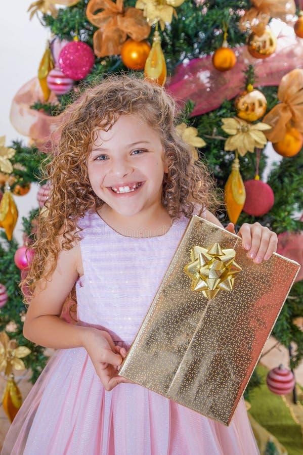Ciérrese para arriba de la muchacha rizada sonriente que lleva un vestido rosado y que sostiene un regalo enorme en sus manos, co fotos de archivo
