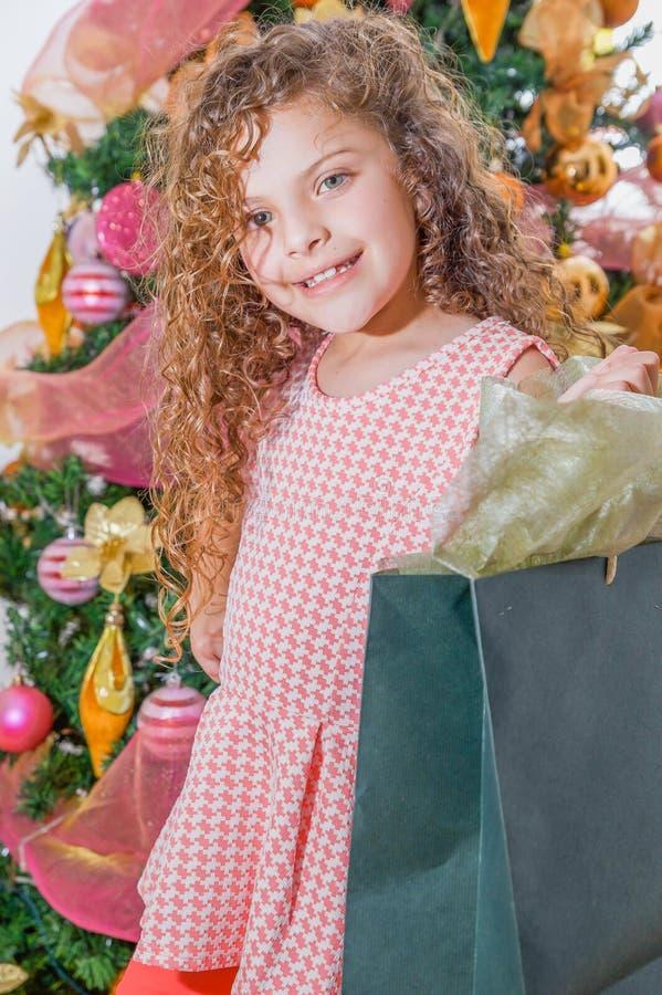 Ciérrese para arriba de la muchacha rizada sonriente que sostiene un bolso enorme del presente, con un árbol de navidad detrás, l foto de archivo
