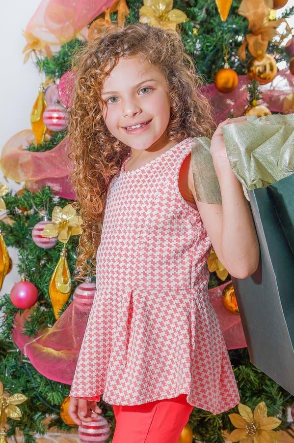 Ciérrese para arriba de la muchacha rizada sonriente que sostiene un bolso enorme del presente, con un árbol de navidad detrás, l fotos de archivo libres de regalías
