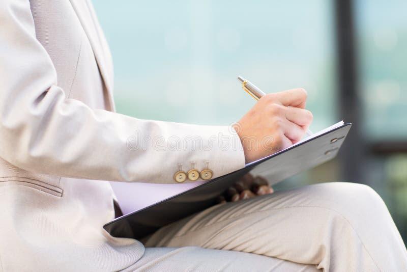 Ciérrese para arriba de la mujer de negocios que escribe al tablero fotos de archivo