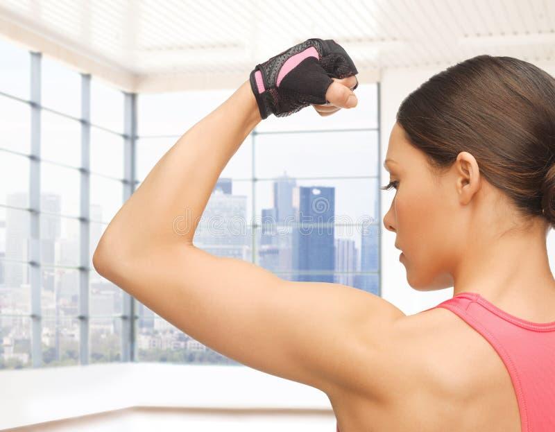 Ciérrese para arriba de la mujer deportiva que dobla su bíceps imagen de archivo