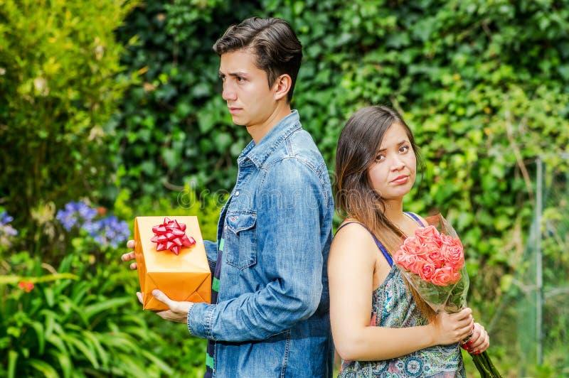Ciérrese para arriba de la mujer enojada que detiene las flores y al hombre enojado que sostienen un regalo de nuevo a la parte p imagen de archivo