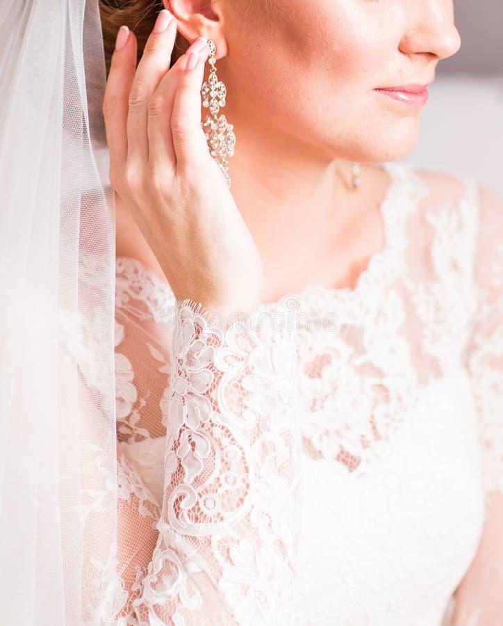 Ciérrese para arriba de la mujer hermosa que lleva los pendientes brillantes del diamante imagenes de archivo